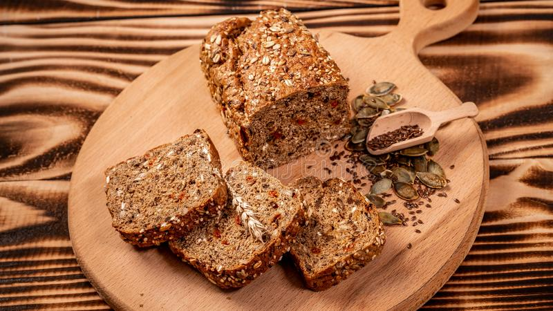 Sliced rye bread on cutting board. Whole grain rye bread with seeds. Ketogenic low carbs diet.  royalty free stock photos