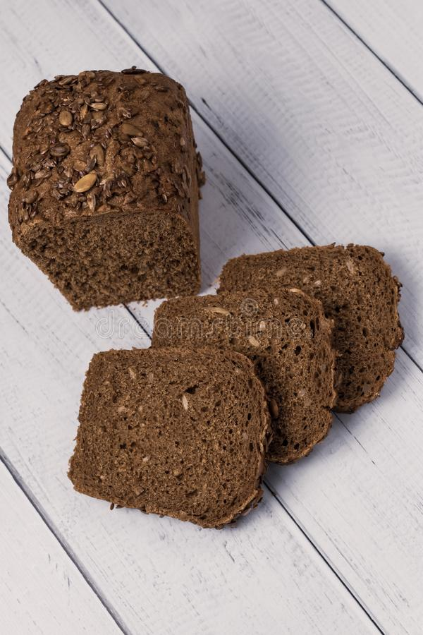 Sliced rye bread with seeds on a white wooden background. The loaf of dark bread. royalty free stock photo