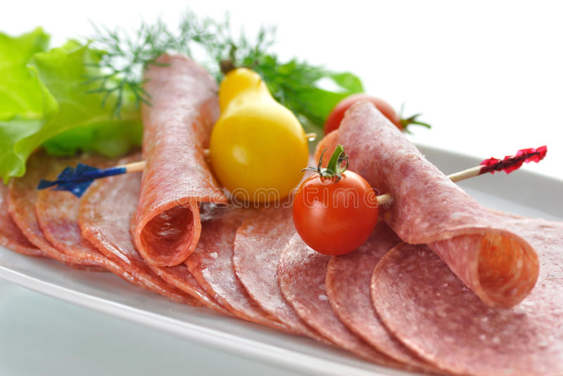 Sliced Salami. With tomatoes and salad leaves stock image