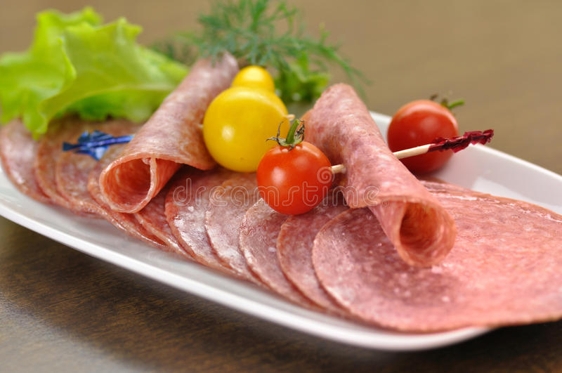 Sliced Salami. With tomatoes and salad leaves stock photos