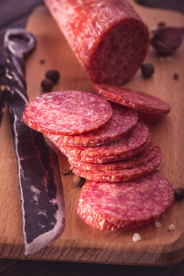 Sliced salami on cutting board closeup. Toned royalty free stock images