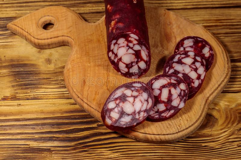 Sliced salami sausage on cutting board on wooden table stock image