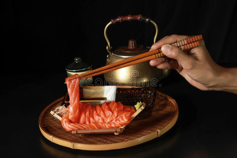 Sliced salmon fish Sashimi in the boat with the chopsticks in the hand on the black wooden table with Brass Teapots and tea cup in royalty free stock photo