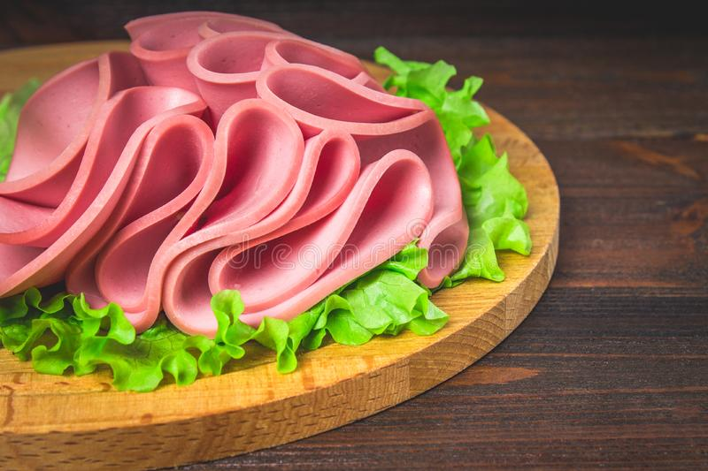 Sliced sausage with salad on a round wooden board. royalty free stock images
