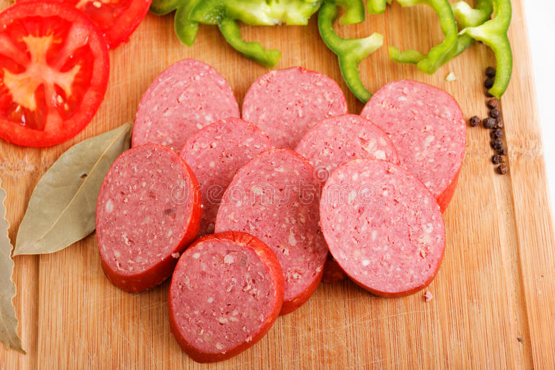 Sliced sausages on chopping board royalty free stock photography