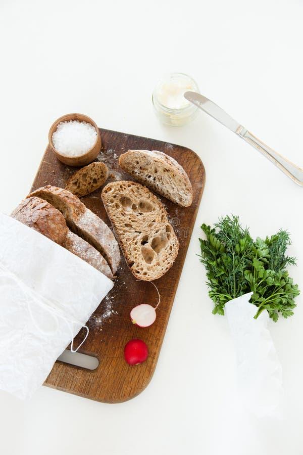 Sliced släntrar av hemlagat bröd, med salt, rädisan, örter och smör på en vit bakgrund royaltyfri bild