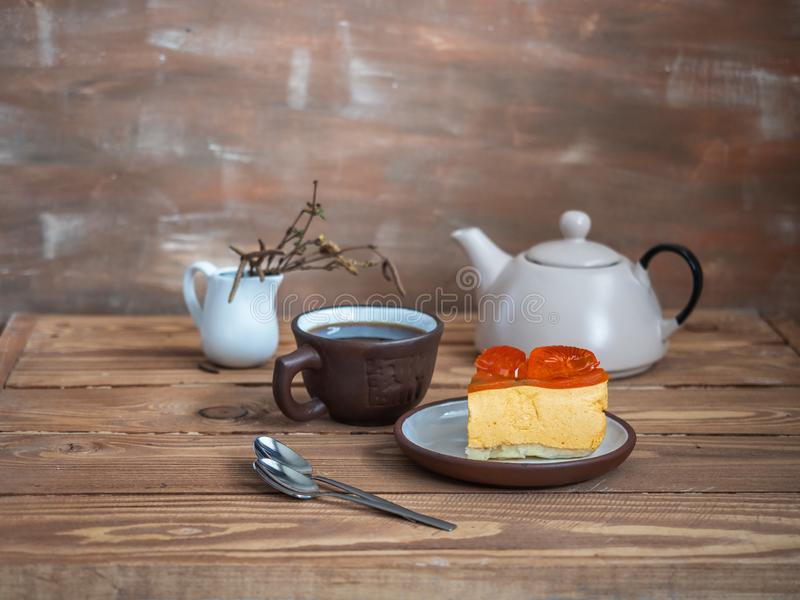 A sliced slice of mozzake cake on a small ceramic bowl, a tea in a brown bowl and a cream teapot in the background. Side. View. Wooden brown background stock images
