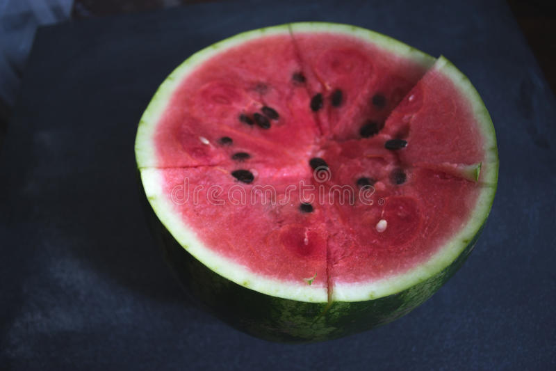 Sliced slices of watermelon on a dark background. stock photography