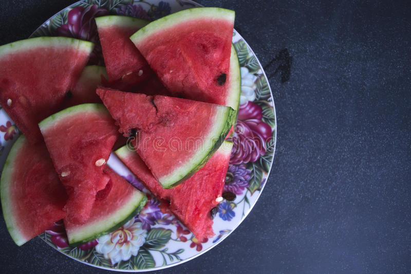 Sliced slices of watermelon on a dark background. stock photo