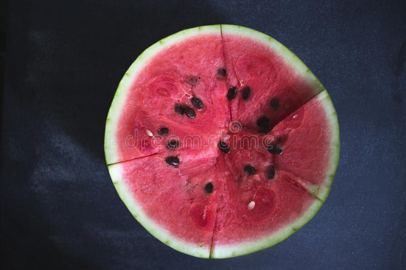 Sliced slices of watermelon on a dark background. royalty free stock photo