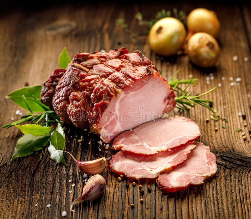 Sliced smoked gammon on a wooden table with addition of fresh herbs and aromatic spices. stock photography