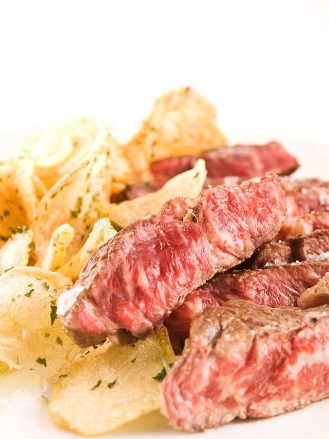 Sliced steak with chips stock photos