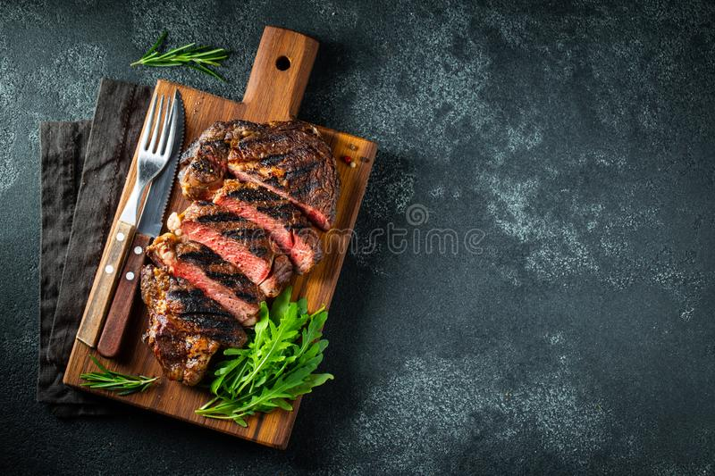 Sliced steak ribeye, grilled with pepper, garlic, salt and thyme served on a wooden cutting Board on a dark stone background. Top royalty free stock image