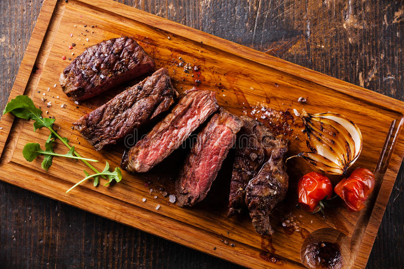 Sliced steak Ribeye with onions and tomatoes royalty free stock image
