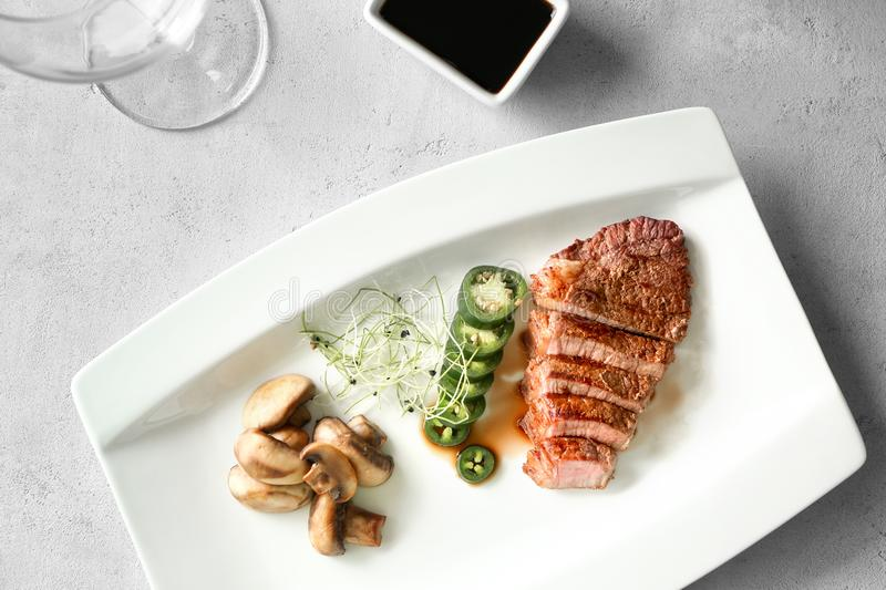 Sliced steak served with vegetables and sauce royalty free stock photo