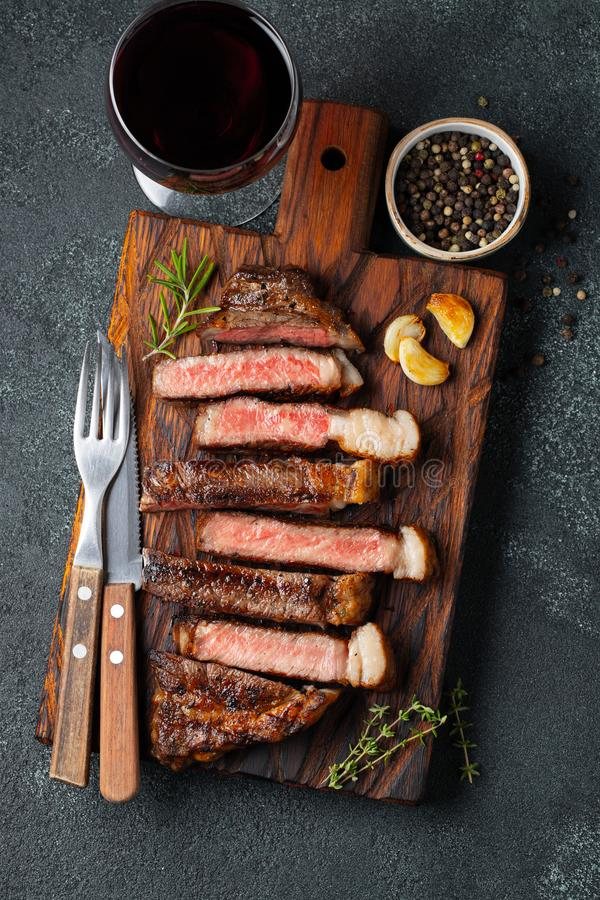 Sliced steak Striploin, grilled with pepper, garlic, salt and thyme served on a wooden chopping Board with a glass of red wine on. A dark stone background. Top royalty free stock image