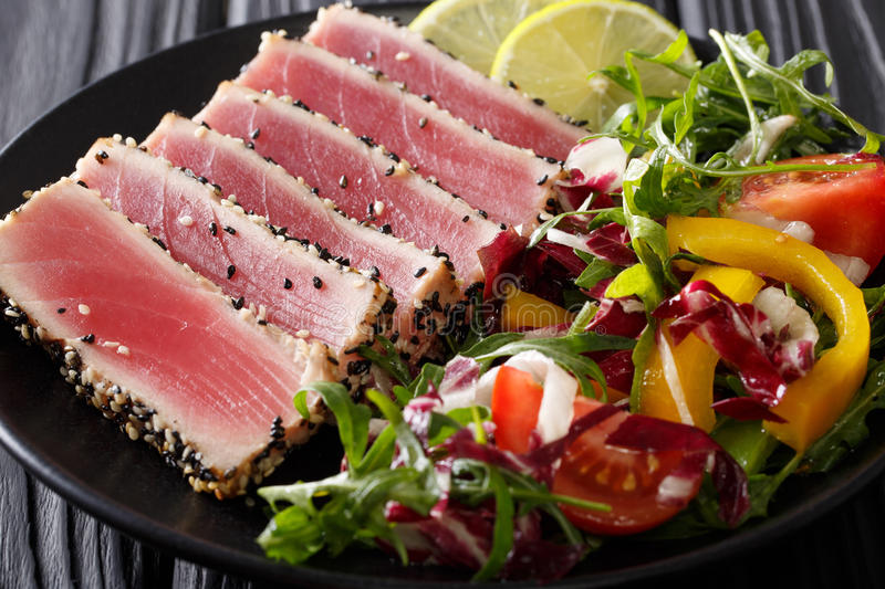 Sliced Steak of tuna in sesame and a salad of fresh vegetables c. Lose-up on a plate. horizontal stock images