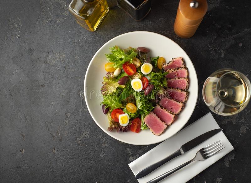 Sliced Steak of tuna in sesame and a salad. Of fresh vegetables and quail eggs stock photo