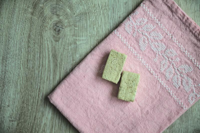 Sliced sunflower halva on a beautiful embroidered pink napkin on a wooden background.  stock photo