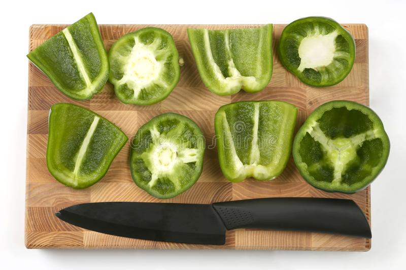 Sliced sweet peppers with a ceramic knife on a wooden board. Healthy and vitamin food royalty free stock photography