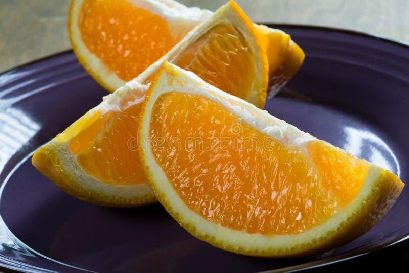 Sliced three orange slices on a rustic table. Closeup stock photo