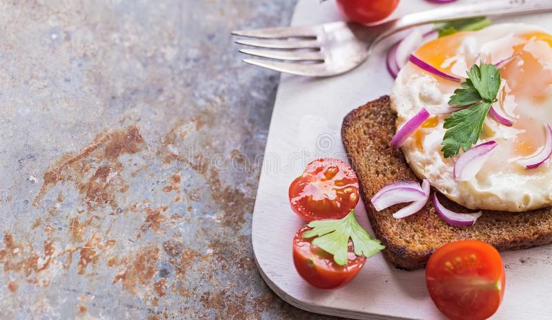 Fried egg toast. Sliced tomato and fried egg toast on old metal background with copy space royalty free stock images