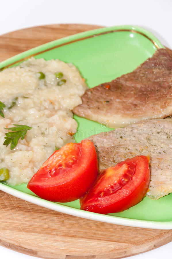 Sliced tomato salad with fried meat and rise risotto stock image