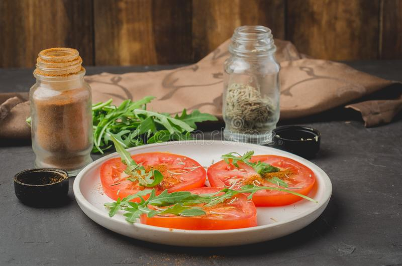 sliced tomatoes and arugula spices salad. Healthy food salad stock photo