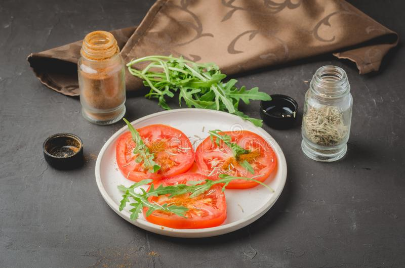 Sliced tomatoes and arugula spices salad. Healthy food on a dark background royalty free stock images
