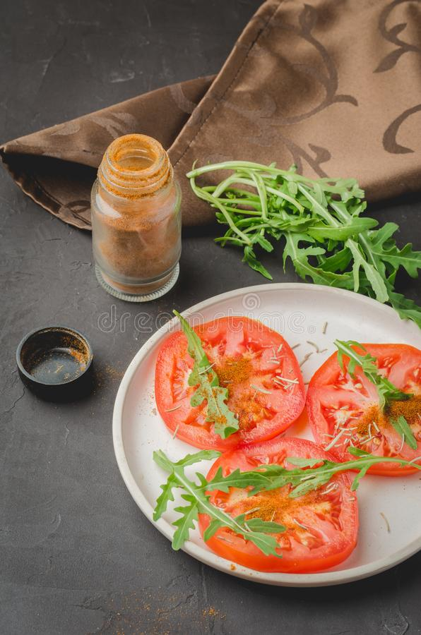 Sliced tomatoes and arugula spices salad. Healthy food salad on a dark background stock photography