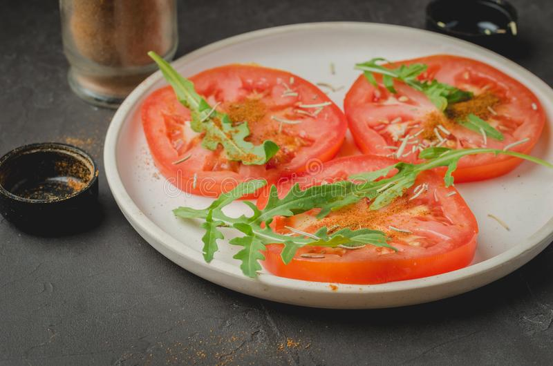 sliced tomatoes and arugula spices salad. Healthy food on a dark background stock photo