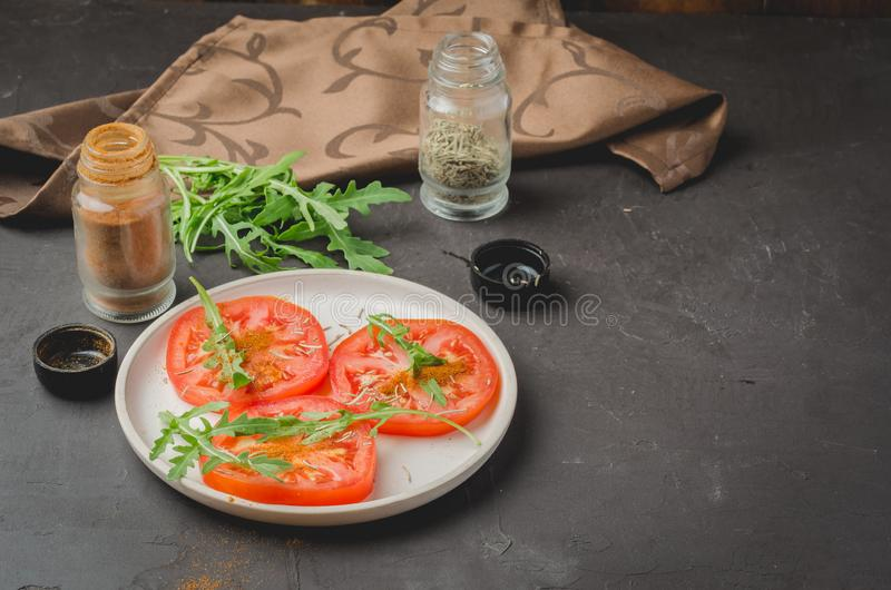 sliced tomatoes and arugula spices salad. Healthy food on a dark background. Copy space stock photography