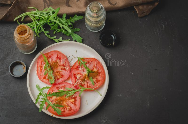 Sliced tomatoes and arugula spices salad. Healthy food salad on a dark background. Copy space and top view stock photos