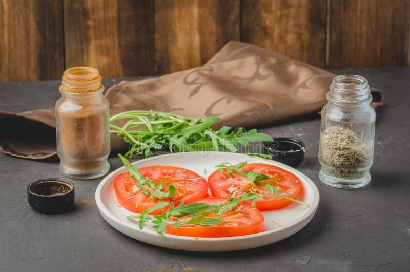 sliced tomatoes and arugula spices salad. Healthy food on a dark background. Selective focus stock photos