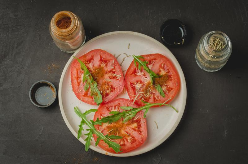 sliced tomatoes and arugula spices salad. Healthy food. Top view royalty free stock photos