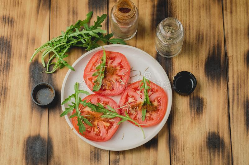 sliced tomatoes and arugula spices salad. In a white bowl on a wooden background. Top view stock photography