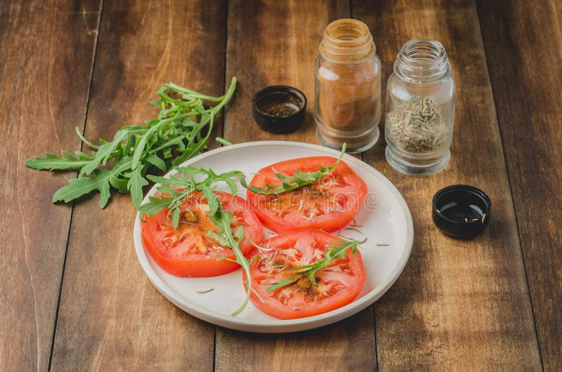 sliced tomatoes and arugula spices salad. In a white bowl on a wooden table. Selective focus stock photography
