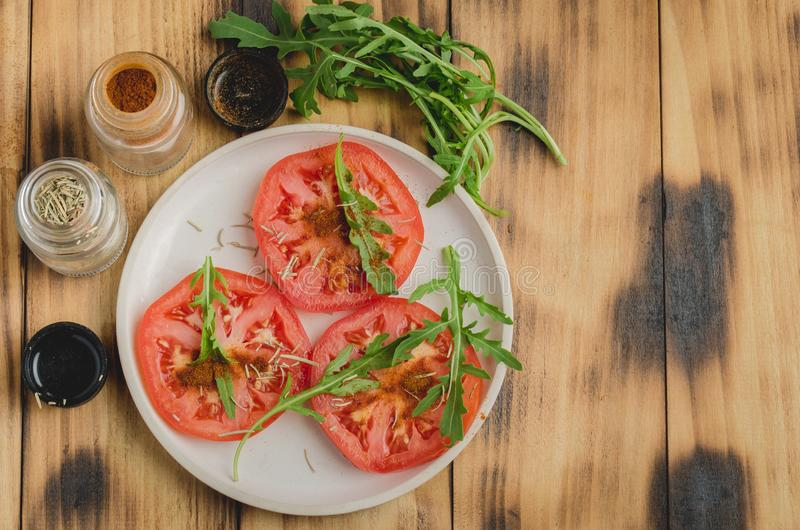 sliced tomatoes and arugula spices salad. In a white bowl on a wooden table. Top view and copy space stock images