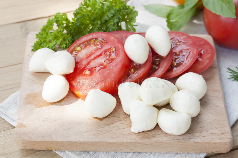 Sliced tomatoes, basil and mozzarella cheese on a wooden board royalty free stock photos