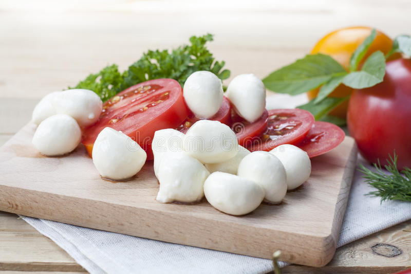 Sliced tomatoes, basil and mozzarella cheese on a wooden board stock image