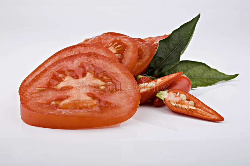 Sliced tomatoes with chili stock images