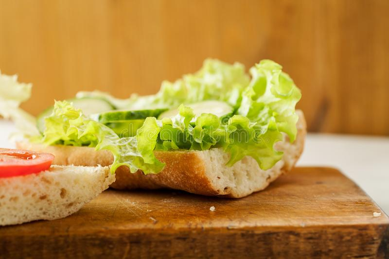 Sliced tomatoes, cucumber and salad leaves on a fresh ciabatta bread royalty free stock photography