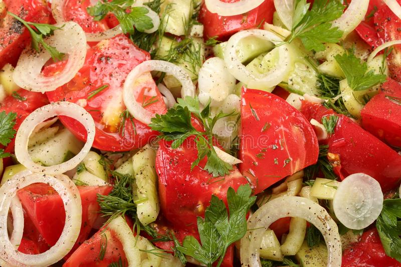 Sliced tomatoes, cucumbers, parsley leaves and dill, spices and olive oil. Fresh vegetable salad close-up stock photos