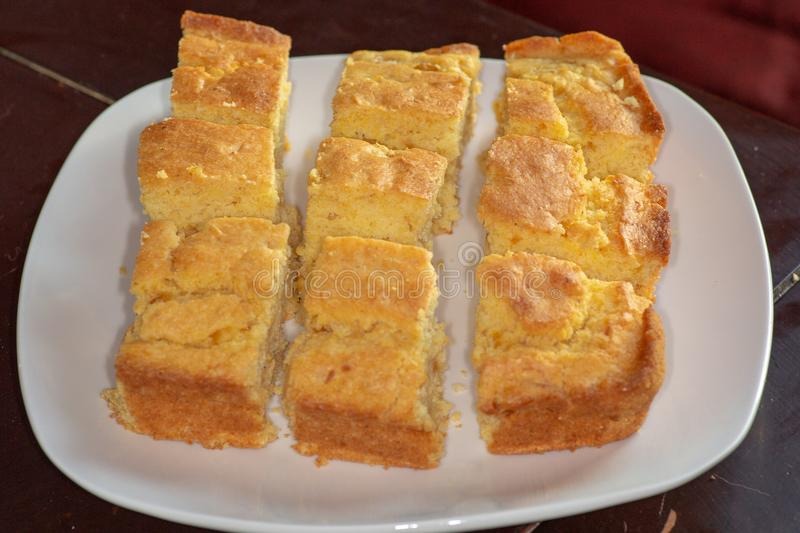 Sliced up corn bread on a white plate on the kitchen table waiting to be eaten stock photos