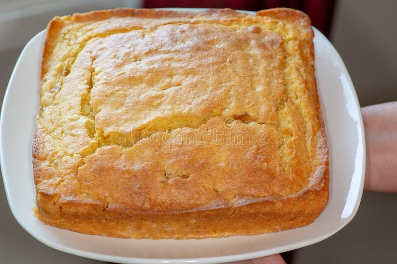 Sliced up corn bread on a white plate on the kitchen table waiting to be eaten royalty free stock photography
