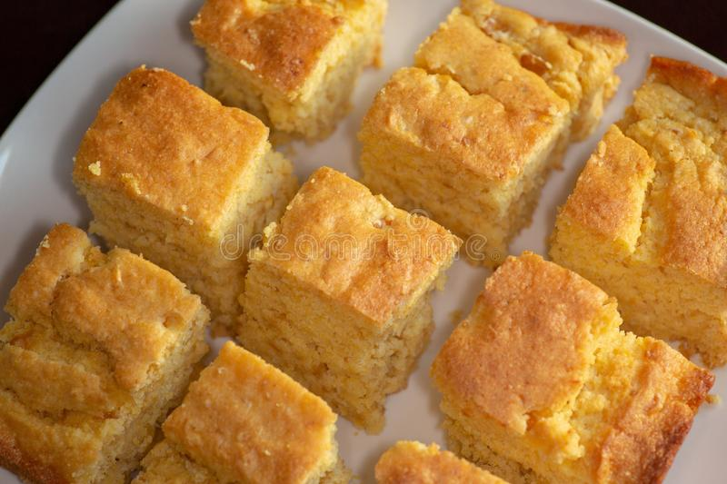 Sliced up corn bread on a white plate on the kitchen table waiting to be eaten stock photo