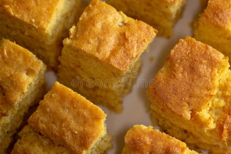 Sliced up corn bread on a white plate on the kitchen table waiting to be eaten stock image