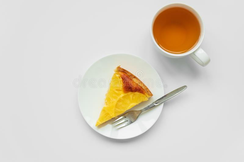 Sliced upside down pineapple cake with cup of tea on white table. Summer tropical dessert. Top view. Copy space royalty free stock photo