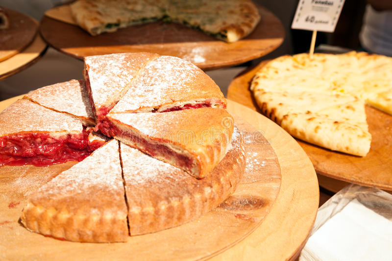 Sliced various pies at food market. Pieces of cut-up fruit pie stock images