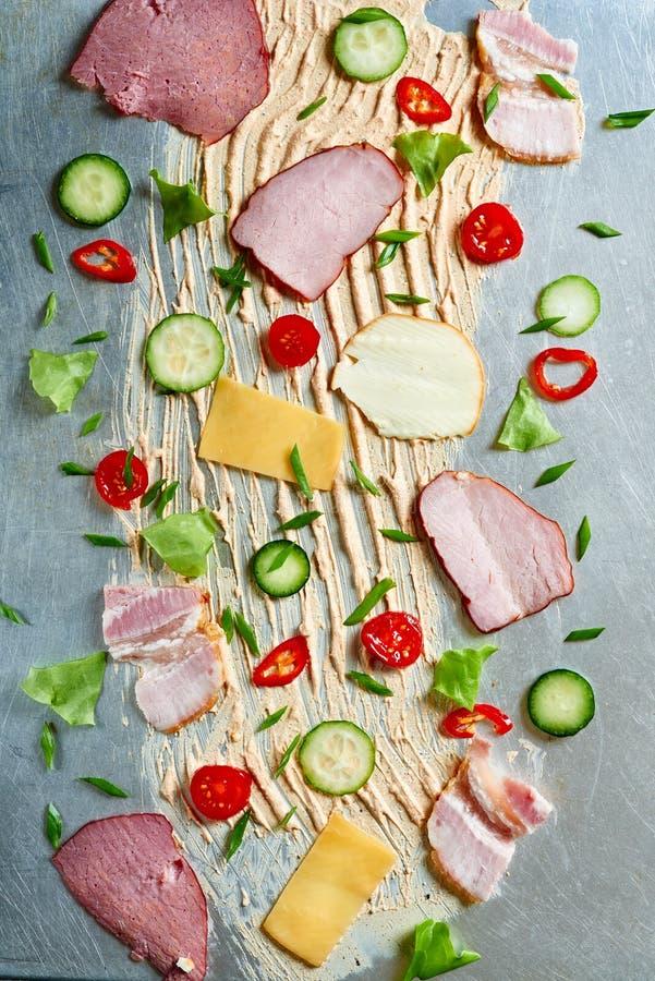 Sliced vegetables, bacon, ham lying on the surface. stock photos